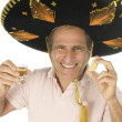 Middle age tourist male wearing Mexican sombrero hat drinking tequila shot - Stock Photo