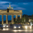 Brandenburg Gate lit with car pedestrian traffic at night on Unter den Linden Berlin Germany Europe - Stock Photo