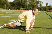 Middle age senior man stretching exercising on sports field — ストック写真