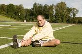 Middle age senior man exercising on sports field — Stock Photo
