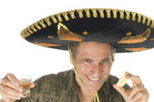 Middle age tourist male wearing Mexican sombrero hat drinking tequila shot — Stock Photo
