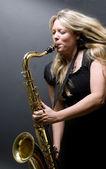 Sexy blonde vrouwelijke saxofoon speler musicus — Stockfoto