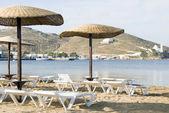 Spiaggia con ombrelloni sedie soggiorno ios isola Cicladi, Grecia — Foto Stock