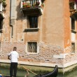 Gondolier on canal Venice Italy - Stock Photo