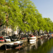 Stock Photo: Canal scene amsterdam reflections boats houses
