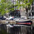 Canal with boats and homes amsterdam holland — Stock Photo #13414387