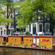 Amsterdam holland canal house boat with flowers — Stock Photo