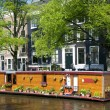 Amsterdam holland canal house boat with flowers — Stock Photo #13414404