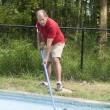 Homeowner cleaning swimming pool — Stock Photo #13417381