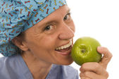 Smiling happy nurse doctor eating green apple — Foto Stock