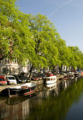 Canal scene amsterdam reflections boats houses — Stock Photo