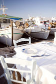 Taverna setting in harbor with fishing boats — Stock Photo