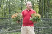 Male homeowner gardening flowers outdoors — Stock Photo