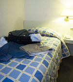 Hotel room with open suitcase — Stockfoto