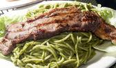 Green spaghetti tallarin saltado steak Peruvian food — Stock Photo