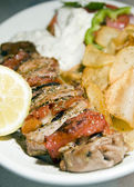 Pork Souvlaki skewer, tzatziki, salad, fried potatoes, photographed, taverna restauarant, Cyclades, Greek island, Greece — Stock Photo