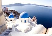Santorini greek island scene with blue dome churches — Stock Photo