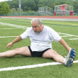 Middle age man stretching and exercising on sports field — Stock Photo #23040764