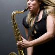 Sexy blond female saxophone player musician — стоковое фото #23041398