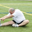 Middle age man stretching and exercising on sports field - Stock Photo