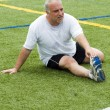 Middle age man stretching and exercising on sports field — Stock Photo #23042376