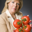 Woman with bunch of fresh ripe tomatoes — Stock Photo