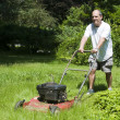 Man cutting grass at suburban house — Stock Photo