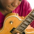 Stock Photo: Young hispanic black womplaying electric guitar
