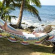 Tourist asleep in hammock by the caribbean sea — Stock Photo #23044198