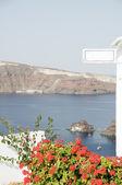 Isla volcánica con vistas al mar con las islas griegas de flores de geranio — Foto de Stock
