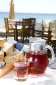 Home made rose wine and crusty bread at greek island taverna — Stock Photo