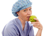 Nurse medical person eating granny smith apple — Stock Photo