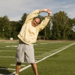 Middle age senior man stretching exercising on sports field — Stock Photo #23057322