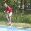 Homeowner cleaning swimming pool — Stock Photo
