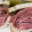 Stock Photo: Corned beef pastrami combination sandwich rye bread pickles