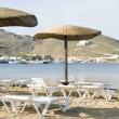 Beach with umbrellas lounge chairs Ios Island Cyclades Greece — Stock Photo #23057482