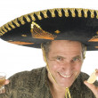 Middle age senior tourist male wearing Mexican somebrero hat drinking tequila shot with slice of lemon — Stock Photo #23058028