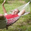 Stock Photo: Smiling middle age mrelaxing in hammock