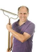 Middle age senior man holding garden bow rake tool — Stock Photo