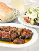 Greek stuffed eggplant and Greek salad crusty bread wine — Stock Photo