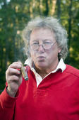 Senior man smoking big cigar — Stock Photo