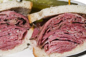 Corned beef pastrami combination sandwich rye bread pickles — Stock Photo
