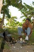 Native man feeding chickens coconut — Stock Photo