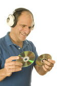 Middle age senior man listening to music through classic head phones — Stockfoto
