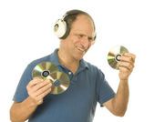 Senior man listening to music cd discs with vintage head phones — Stock Photo