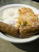 Fried eggs over easy pork sausages home fried potatoes breakfast — Stock Photo