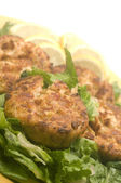 Lobster cakes bed of lettuce with lemon slice wedges — Stock Photo