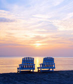 Sunset on Picnic Center beach lounge chairs and boats — Stock Photo