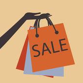 Hand halten einkaufstaschen zu verkaufen — Stockvektor