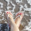 Woman Feet with flip flops on the Beach - Stock Photo
